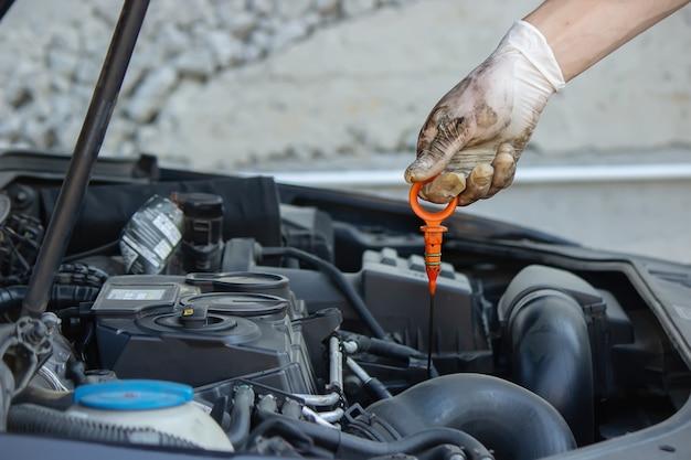 Un meccanico che cambia olio versa olio nel motore di un'auto.