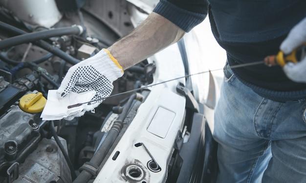 Meccanico automobilistico che controlla il livello dell'olio motore dell'auto
