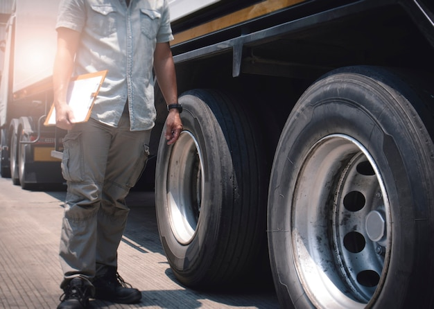 L'autista del meccanico automatico che tiene gli appunti sta controllando la sicurezza dell'ispezione del camion di ruote e pneumatici di un camion