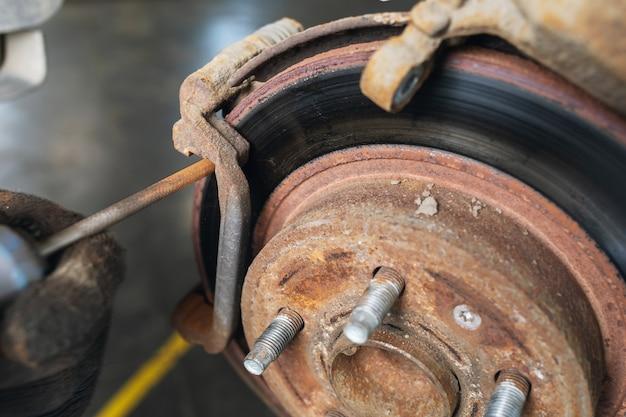 Un meccanico macina la ruggine sui dischi dei freni prima di sostituire le pastiglie, primo piano