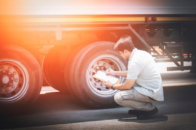 Gli appunti della tenuta del meccanico automatico stanno controllando un camion ruote pneumatici ispezione sicurezza manutenzione