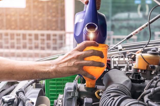 Il meccanico sta riempiendo l'olio motore dell'auto all'interno del centro di riparazione auto, nell'industria automobilistica e nelle idee di garage.