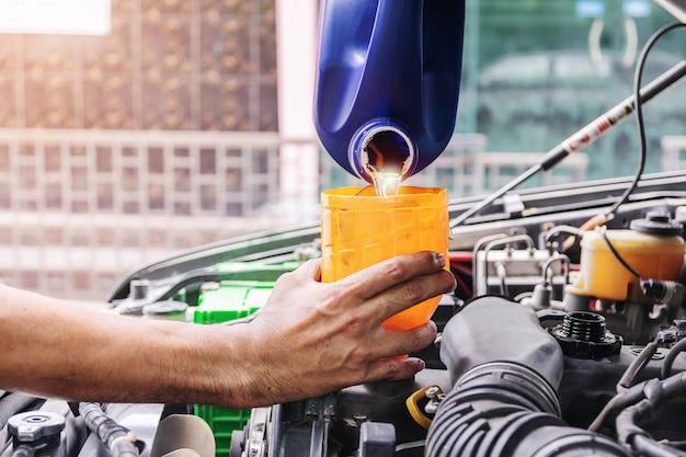 Il meccanico sta riempiendo l'olio motore dell'auto all'interno del centro di riparazione auto