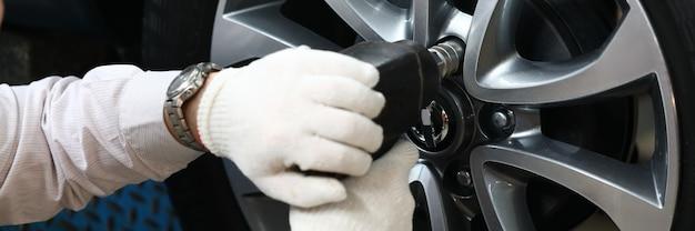 Il meccanico auto sta riparando il disco della ruota dell'auto