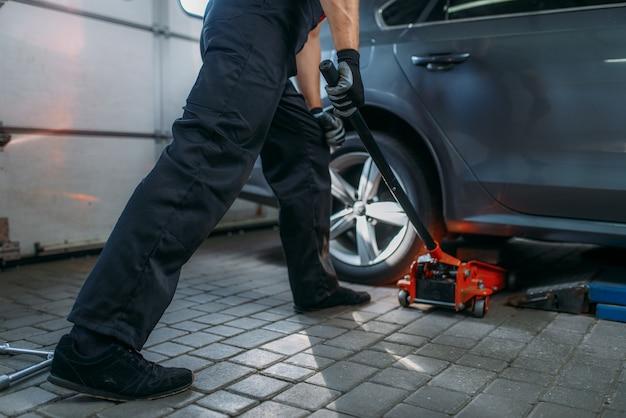 Il meccanico auto solleva l'auto in servizio di pneumatici