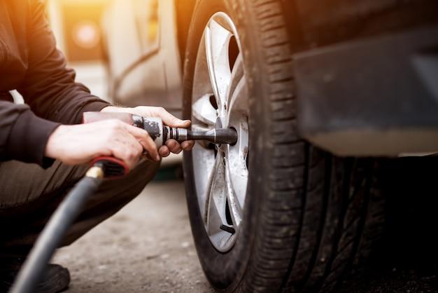 Uomo meccanico automatico con cacciavite elettrico che cambia pneumatico all'esterno. servizio auto. le mani sostituiscono i pneumatici sulle ruote. concetto di installazione di pneumatici.