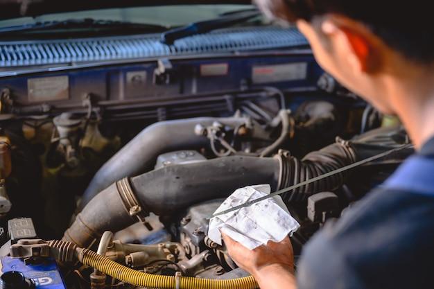 Il meccanico automatico tira l'indicatore del livello dell'olio per il cambio dell'olio dell'auto in garage