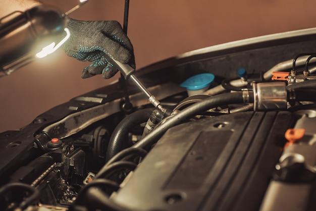 Il meccanico ripara l'auto. il dipendente esegue la manutenzione della macchina.