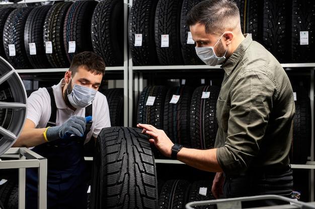 Il meccanico automobilistico parla dei vantaggi del pneumatico per auto al giovane cliente in servizio, l'uomo è venuto a comprare un nuovo pneumatico per la sua automobile, sta parlando ed esamina il prodotto, indossa una maschera medica durante la quarantena