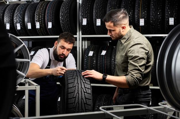 Il meccanico automobilistico parla dei vantaggi del pneumatico per auto al giovane cliente in servizio, l'uomo è venuto a comprare un nuovo pneumatico per la sua automobile, sta parlando ed esaminando il prodotto