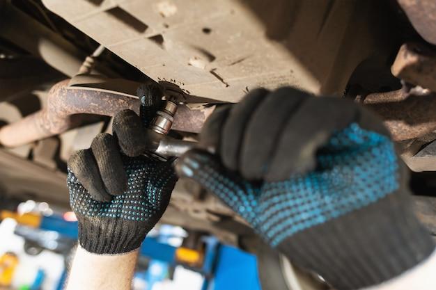 Un meccanico stringe il tappo di scarico dell'olio nel carter dell'auto con una chiave dinamometrica, primo piano