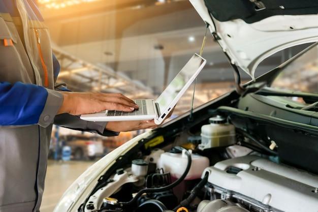 Meccanico automobilistico utilizza la tecnologia informatica per la riparazione automatica nei centri di assistenza auto