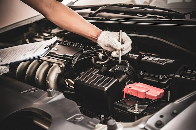 Meccanico automobilistico che utilizza la lista di controllo per i sistemi del motore dell'auto dopo la correzione