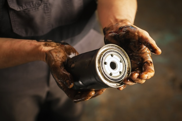 Meccanico automatico con le mani sporche e il filtro dell'olio. manutenzione del servizio.
