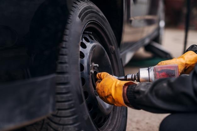 Meccanico auto con cacciavite elettrico che cambia pneumatico all'esterno. servizio auto. installazione di pneumatici.