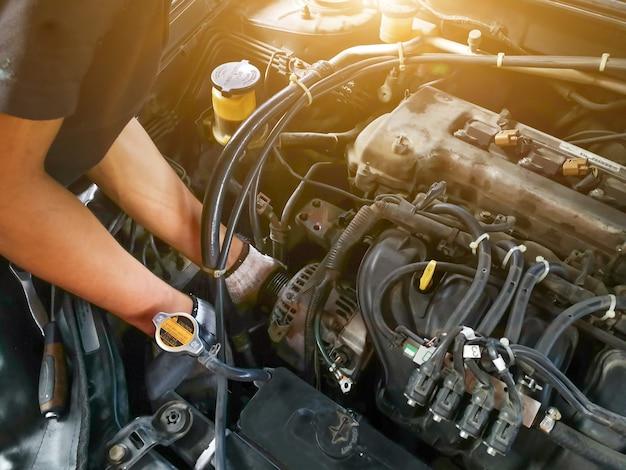 Meccanico di automobile con controllo di lavoro dello strumento e riparato un vecchio motore di automobile alla stazione di servizio, cambio e riparazione prima di guidare