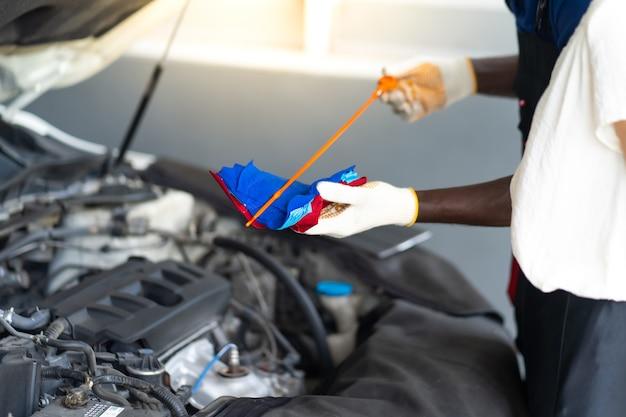 Operaio meccanico automatico che controlla il livello dell'olio nel motore dell'auto. manutenzione auto e concetto di garage di servizio auto.