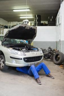 Meccanico auto che lavora sotto auto