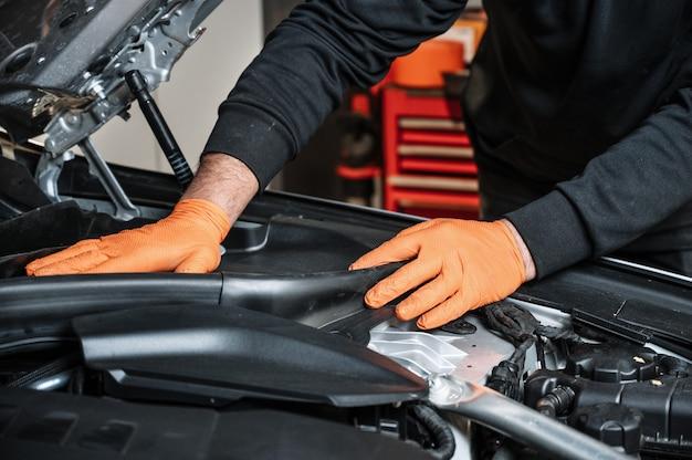 Meccanico di automobile che lavora e ripara il motore di automobile nel garage della meccanica. servizio auto.