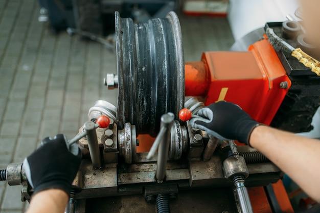 Il meccanico di auto lavora con la ruota sgualcita sulla macchina di laminazione del disco, servizio di riparazione dei pneumatici operaio ripara pneumatici per auto in garage, ispezione automobilistica professionale in officina