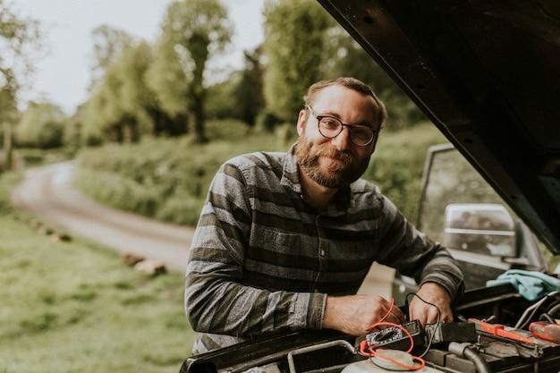 Uomo di riparazione auto che ripara il motore dell'auto all'aperto