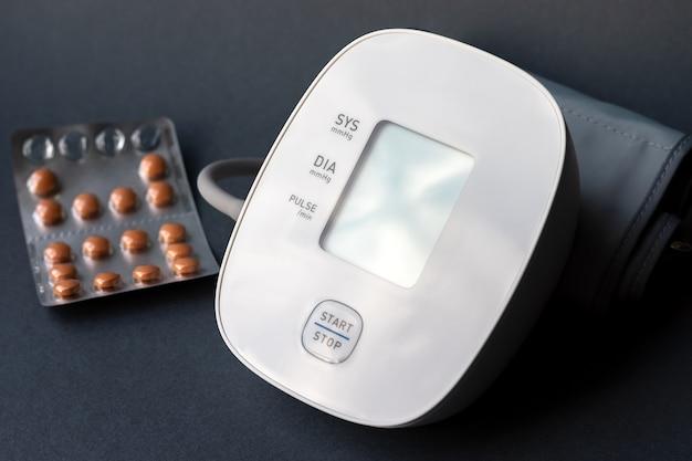 Monitor automatico della pressione sanguigna e blister con pillole su sfondo grigio scuro. tonometro elettronico medico