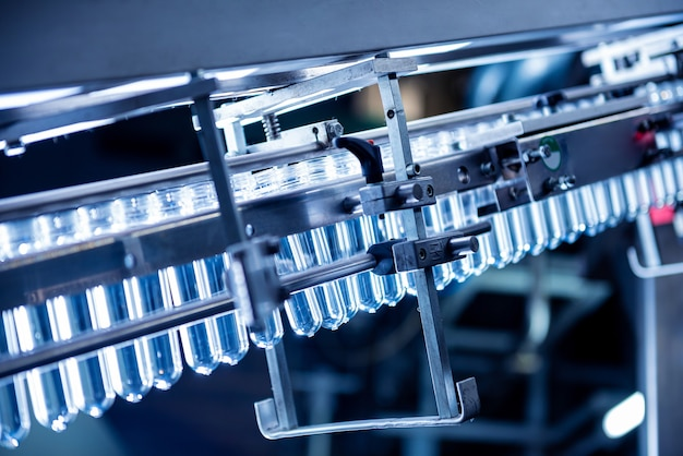 La riempitrice automatica versa l'acqua in bottiglie di plastica per animali domestici in un moderno impianto di bevande
