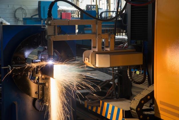 La macchina laser automatica taglia il profilo metallico, primo piano. sistema di taglio tubi