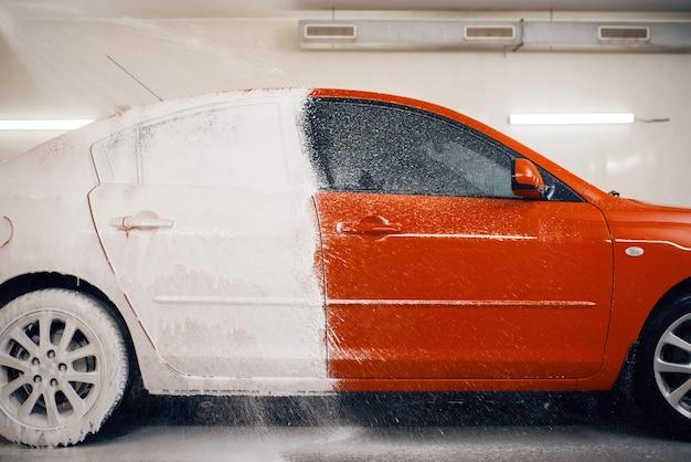 L'auto è per metà in schiuma, servizio di autolavaggio. automobile sulla stazione di autolavaggio, concetto di business autolavaggio