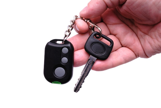 Chiavi dell'automobile e pannello di controllo remoto dal sistema di allarme dell'auto in una mano.