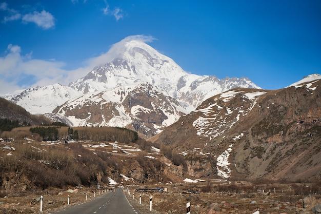 Strada di montagna dell'automobile fino al fondo del monte kazbegi. tappo di neve sulla cima della montagna.