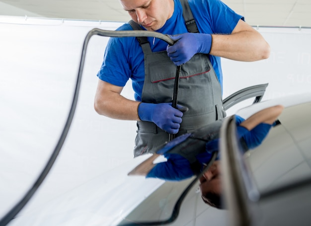 I lavoratori speciali automobilistici rimuovono il vecchio parabrezza o il parabrezza di un'auto nel garage automatico della stazione di servizio.