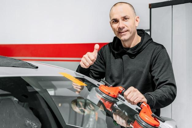 Operaio tecnico automobilistico che sostituisce il parabrezza o il parabrezza di un'auto nel garage della stazione di servizio auto.