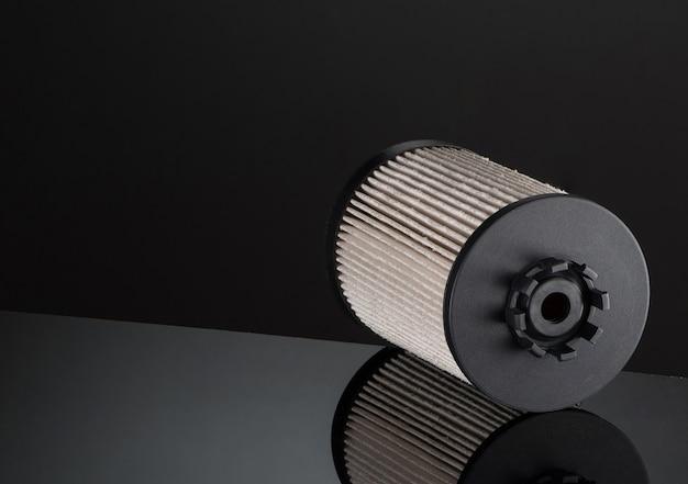 Filtro automobilistico di forma cilindrica su sfondo nero con riflessione