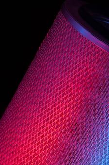 Colori rossi di forma cilindrica del filtro automobilistico su un primo piano nero del fondo