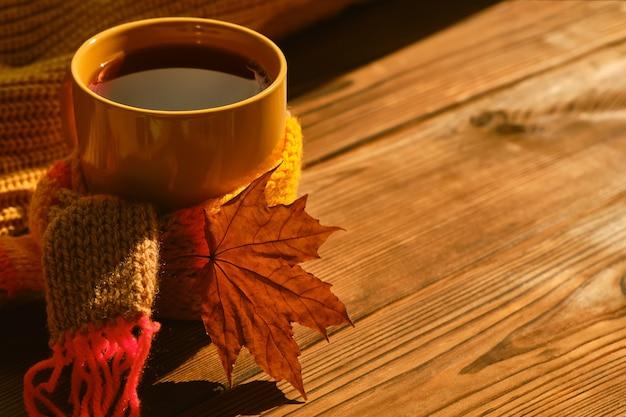 Sfondo autunnale - tazza di tè con sciarpa calda e foglia autunnale secca sotto la luce del sole morbida sul tavolo di legno. concetto di trascorrere il tempo autunnale in una casa accogliente, copia spazio