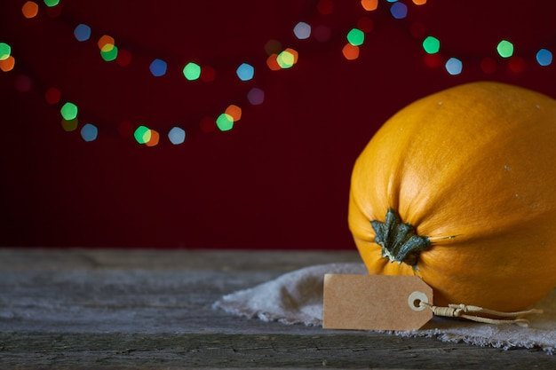 Sfondo autunnale su una superficie di legno scuro, zucca gialla su uno sfondo di luci sfocate