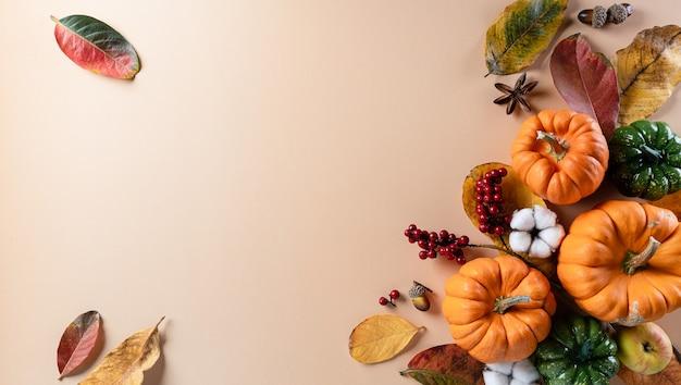 Decorazione di sfondo autunnale da foglie secche e zucca con spazio di copia