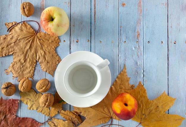 Sfondo autunnale di foglie secche con tazza di caffè o tè, mela, nettarina, noci.