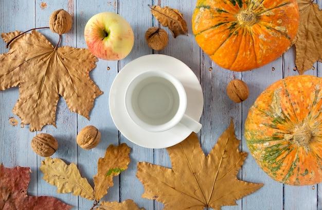 Sfondo autunnale di foglie secche con tazza di caffè o tè, piccole zucche, mele, noci