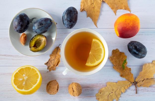 Sfondo autunnale di foglie secche con tazza bianca, limone, prugne mature e nettarine, noci.