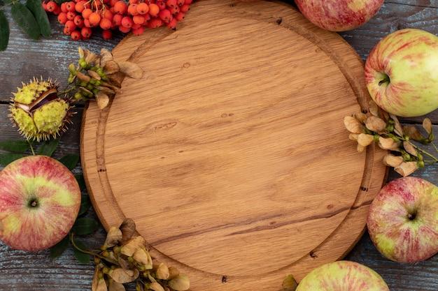Sfondo autunnale da foglie cadute e frutti con impostazione di posto vintage sul vecchio tavolo in legno. concetto di giorno del ringraziamento.