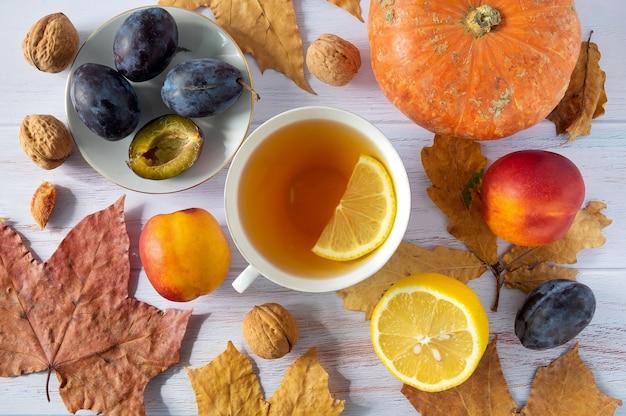 Sfondo autunnale di foglie con tazza di tè, piccola zucca, limone, prugne, nettarine, noci
