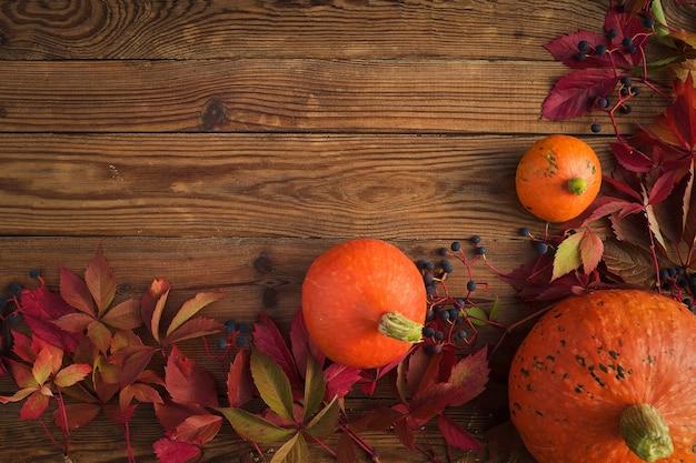 Sfondo autunno - zucche arancioni con foglie rosse su un tavolo di legno. vista dall'alto, copia spazio e concetto di ringraziamento.