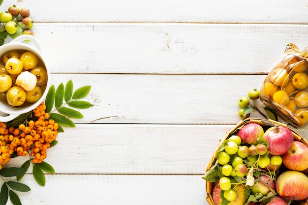 Sfondo autunnale... mele del paradiso in sciroppo di zucchero su un tavolo di legno bianco. raccolta del raccolto autunnale. marmellata di mele del paradiso. vista dall'alto. copia spazio.