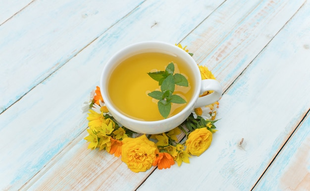 Sfondo autunnale. tazza da tè con menta e fiori autunnali su uno sfondo di legno. concetto autunno tempo autunno