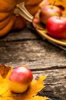 Sfondo autunnale con mele zucca e foglia d'acero su un vecchio tavolo di legno concetto del giorno del ringraziamento