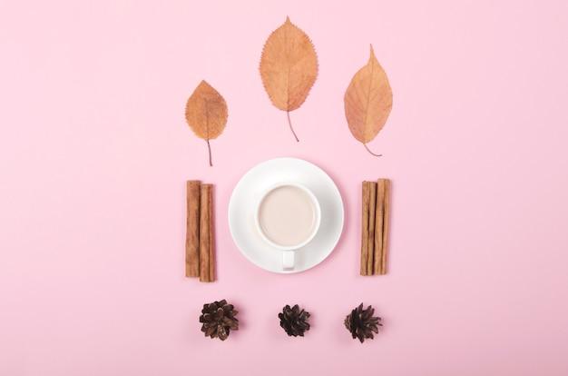 Sfondo autunno con caffè, cannella e foglie su sfondo rosa