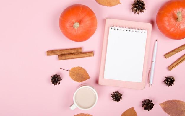 Sfondo autunnale con blocco note, zucca arancione, cannella e foglie su sfondo rosa