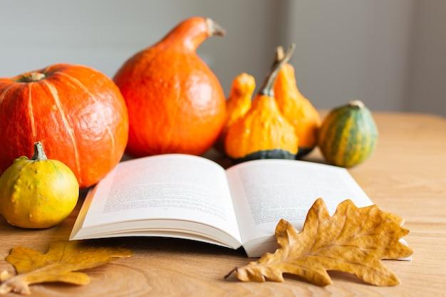 Sfondo autunnale con libro aperto e zucche arancioni con foglie